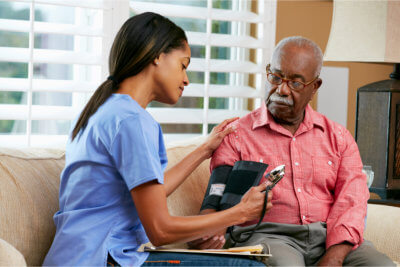 medical staff monitoring elderly man's blood pressure